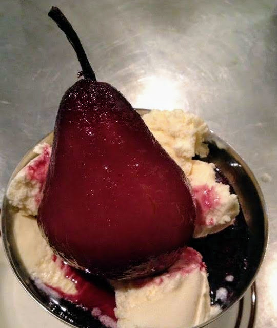 Pears poached in red wine and served over vanilla ice cream